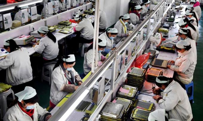 Công nhân đeo khẩu trang làm việc trong một nhà máy điện tử ở tỉnh Thẩm Tây (Trung Quốc) hôm 4/3. Ảnh: AP