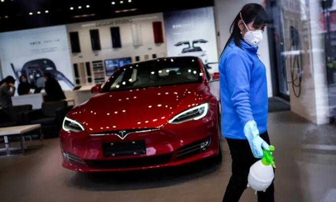 Nhân viên vệ sinh một cửa hàng tại Thượng Hải của Tesla, một trong những doanh nghiệp trở lại sản xuất sớm nhất Trung Quốc. Ảnh: Reuters
