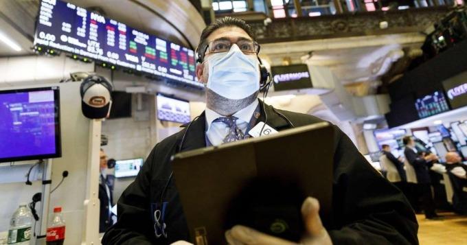 Một nhân viên giao dịch trên sàn New York đeo khẩu trang trong phiên ngày 19/3. Ảnh: EPA