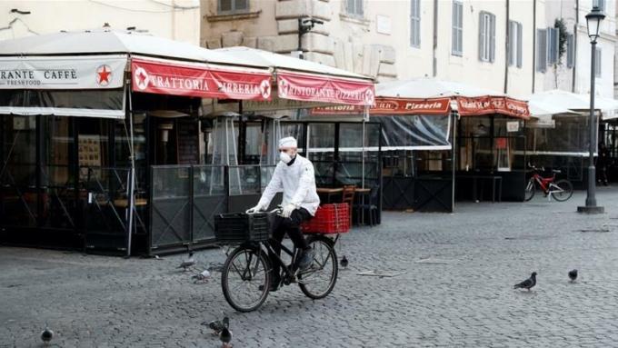 Nhân viên giao hàng đi qua một con phố vắng vẻ ở Rome (Italy). Ảnh: Reuters