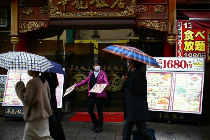 Nhân viên mời khách bên ngoài một nhà hàng ở Yokohama (Nhật Bản). Ảnh: Reuters