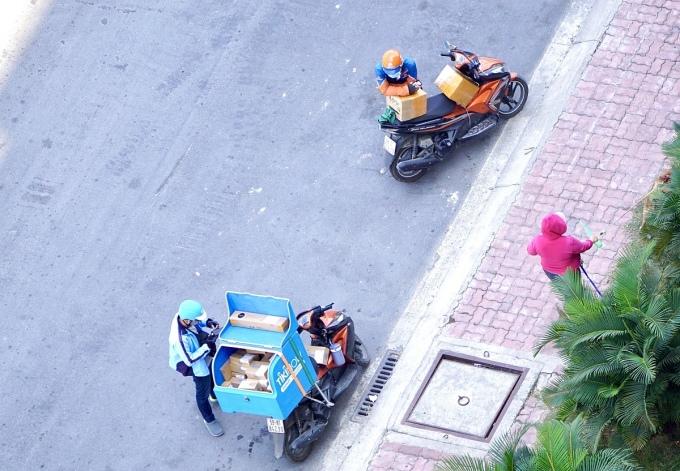 Nhân viên giao hàng các công ty thương mại điện tử chờ khách tại một chung cư ở quận 8, TP HCM. Ảnh: Viễn Thông