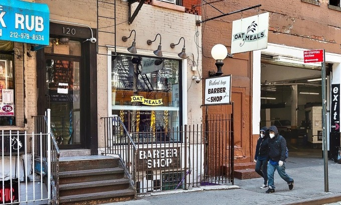 Người đi bộ đeo khẩu trang trên một con phố vắng lặng với nhà hàng, tiệm làm tóc đều đóng cửa ở New York. Ảnh: NYT
