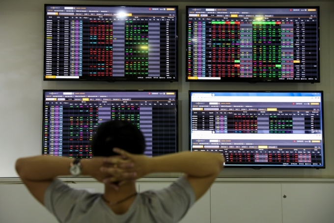 Nhà đầu tư quan sát bảng giá điện tử tại một sàn chứng khoán ở TP HCM.Ảnh: Như Quỳnh.