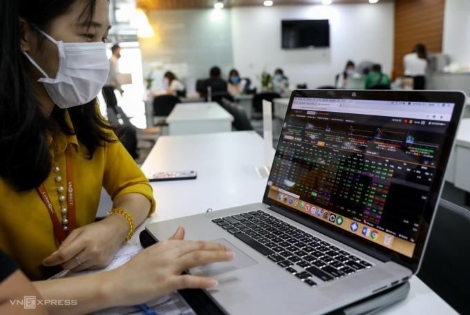 Nhân viên môi giới VNDIRECT hướng dẫn khách hàng mới theo dõi bảng điện tử. Ảnh: Quỳnh Trần.