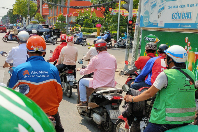 Tài xế của hàng loạt hãng giao hàng, gọi xe chờ đèn đỏ tại ngã tư Cách Mạng Tháng Tám - Nguyễn Đình Chiều, quận 3, TP HCM chiều 12/5. Ảnh: Viễn Thông