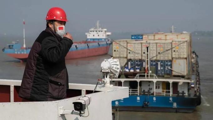 Công nhân đeo khẩu trang giám sát hàng hóa tại một càng trên sông Dương Tử, Trung Quốc vào tháng 4/2020. Ảnh: AFP.
