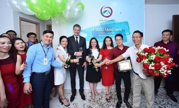 Ông Nguyễn Hải (áo xanh, hàng đầu) trong sự kiện Oriflame thưởng nhà cho bà Phan Thị Thủy (váy đỏ đứng giữa).