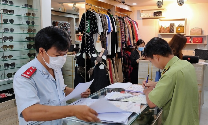 Đoàn kiểm tra lập biên bản vi phạm tại một địa điểm kinh doanh trên đường Sư Vạn Hạnh, quận 10, TP HCM sáng ngày 22/5. Ảnh: Dỹ Tùng