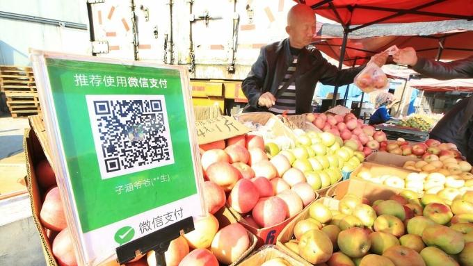 Một người bán quả tại Đại Liên nhận thanh toán bằng mã QR. Ảnh: Nikkei