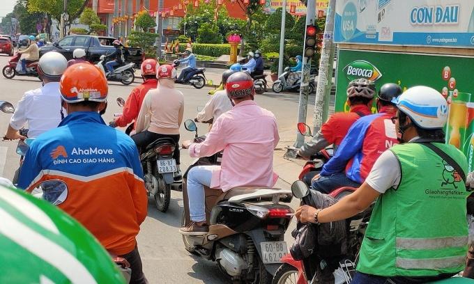 Tài xế của AhaMove, Giaohangtietkiem, GoViet, Now, Grab...dừng xe ở một ngã tư tại quận 3, TP HCM vào ngày 12/5. Ảnh: Viễn Thông
