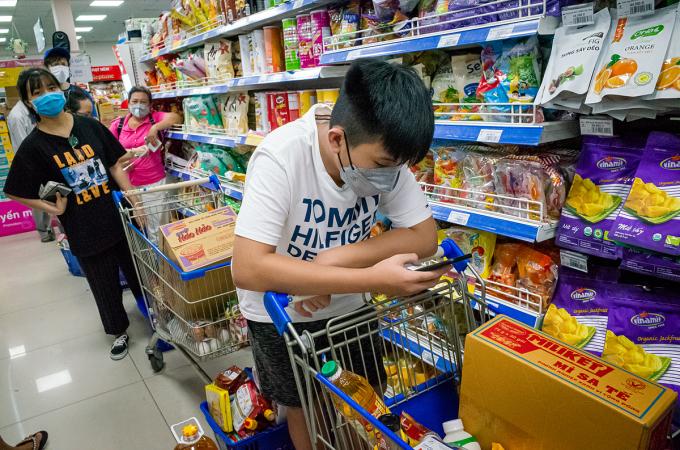 Người dân xếp hàng mua thực phẩm tại siêu thị Coop Mart Cống Quỳnh (quận 1, TP HCM) tối 31/3. Ảnh: Thành Nguyễn