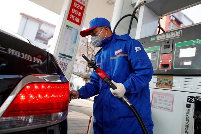 Một nhân viên trạm xăng đeo khẩu trang chuẩn bị bơm xăng cho khách tại Bắc Kinh, Trung Quốc vào tháng 2/2020. Ảnh: Reuters
