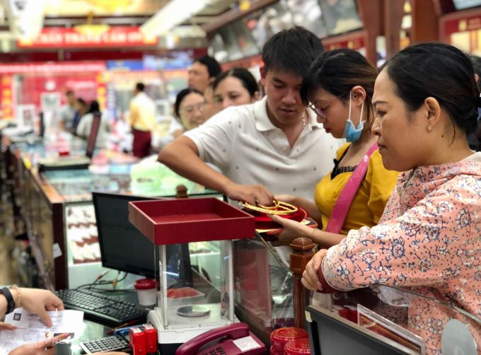 Cặp vợ chồng bán vàng tại cửa hàng chiều 22/7. Ảnh: Quỳnh Trang.