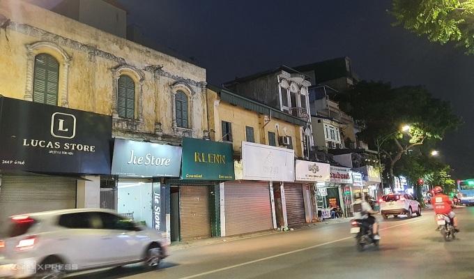 5 cửa hàng thời trang sát nhau trên Phố Huế lúc 19h tối trong tình trạng đóng cửa. Cửa hàng thứ 4 đã dỡ bảng hiệu kinh doanh. Ảnh: Phương Ánh.