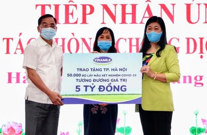 Đại diện Sở Y tế và Mặt trận Tổ quốc thành phố Hà Nội tiếp nhận 50.000 bộ lấy mẫu xét nghiệm Covid-19, tương đương 5 tỷ đồng từ đại diện Vinamilk.