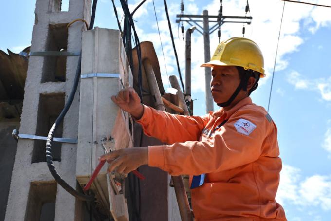 Công nhân Điện lực Mê Linh (Hà Nội) thao tác chuẩn bị ghi chỉ số công tơ. Ảnh: Anh Minh