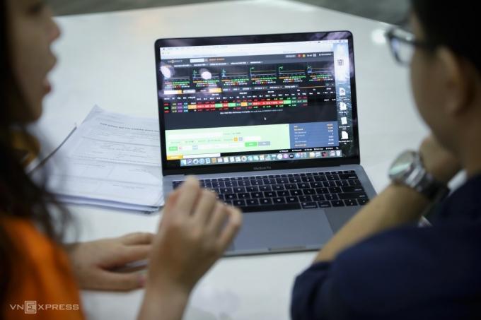 Nhân viên môi giới của Công ty Chứng khoán VNDIRETC hướng dẫn nhà đầu tư mở tài khoản chứng khoán. Ảnh: Quỳnh Trần.