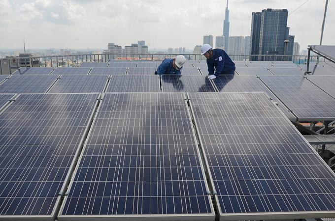 Công nhân lắp đặt một dự án điện mặt trời mái nhà tại TP HCM. Ảnh: EVNHCM.
