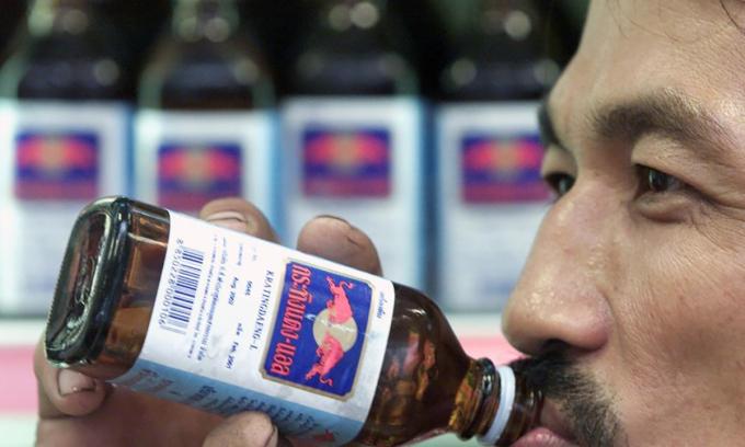 Một người đàn ông Thái Lan uống Krating Daeng - phiên bản gốc của Red Bull tại một cửa hàng tiện lợi ở Bangkok năm 2001. Ảnh Reuters