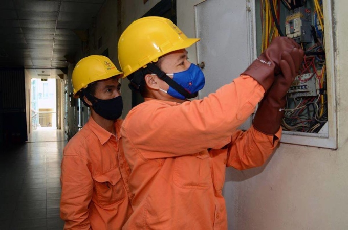 Công nhân Điện lực Hà Nội kiểm tra công tơ điện tại nhà khách hàng. Ảnh: Trung Trần.