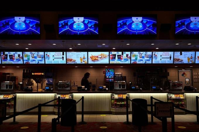 Khu vực bán đồ ăn vắng người trong một rạp phim đã mở lại ở Mỹ. Ảnh: NYT