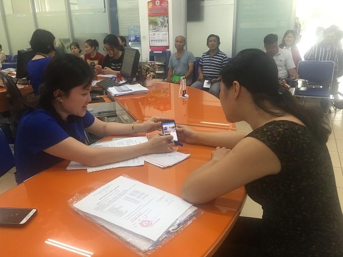 Nhân viên EVNHCMC hướng dẫn khách hàng sử dụng app chăm sóc khách hàng của EVNHCMC.