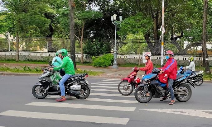 Tài xế các ứng dụng gọi xe, gọi đồ ăn trên đường phố TP HCM. Ảnh: Viễn Thông.