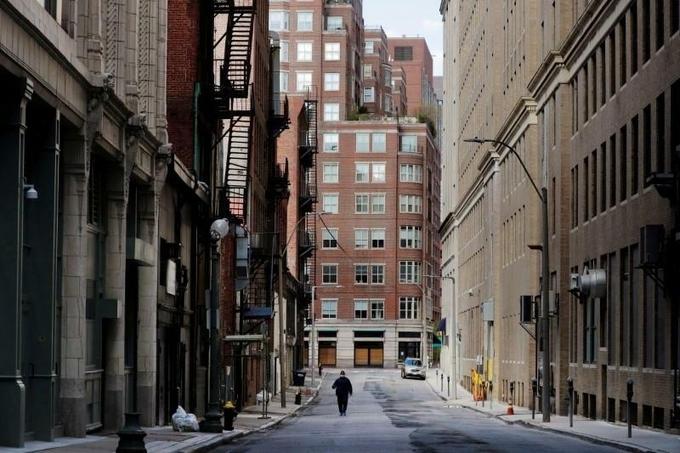 Người đi bộ trên một con phố vắng vẻ vì đại dịch tại Massachusetts. Ảnh: Reuters