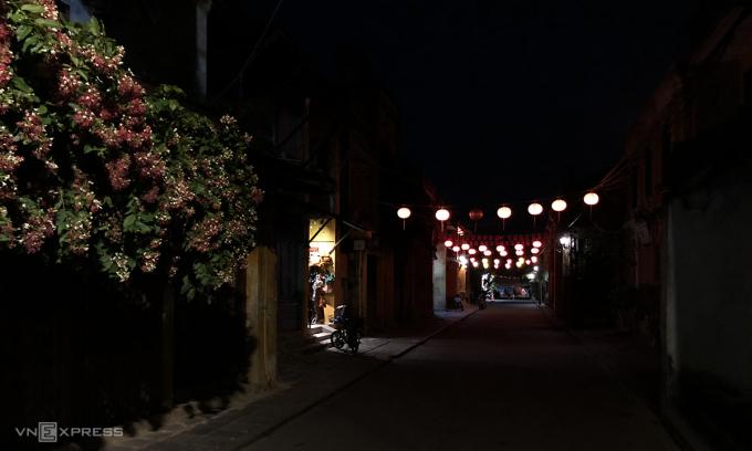 Một góc phố Nguyễn Thái Học tối om, chỉ còn vài cửa hàng mở cửa lúc 18h tối Chủ nhật (28/3). Ảnh: Anh Tú