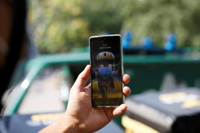 Một tài xế Meituan quét gương mặt trên ứng dụng trước khi bắt đầu làm việc. Ảnh: Reuters.