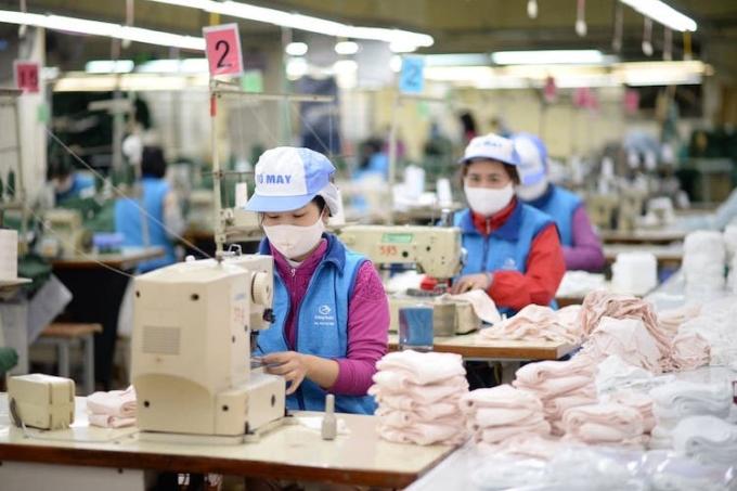 Công nhân Công ty Dệt kim Đông Xuân sản xuất khẩu trang vải mùa dịch. Ảnh: Công Nam