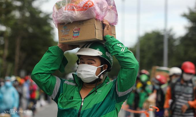 Shipper đứng xếp hàng chờ giao đồ trước bệnh viện dã chiến số 6 (TP Thủ Đức). Ảnh: Thành Nguyễn.