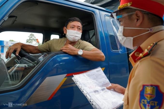 Cảnh sát giao thông kiểm tra giấy xét nghiệm âm tính Covid-19 của tài xế chở hàng tại Đồng Tháp, sáng 20/7. Ảnh:Ngọc Tài
