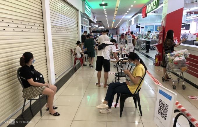 Khách ngồi chờ tới lượt vào mua hàng tại siêu thị Go!Market (Nguyễn Xiển, Thanh Xuân). Ảnh: Anh Tú