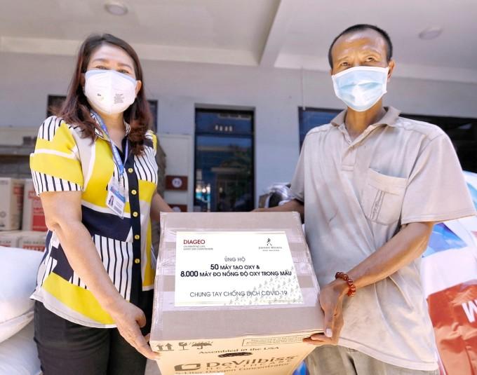 Đại diện Mặt trận Tổ quốc tại TP HCM (bên trái) nhận thiết bị y tế điều trị bệnh nhân Covid-19 tại Ủy ban nhân dân quận Gò Vấp ngày 16/8/2021