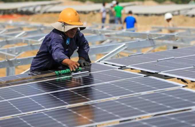 Công nhân lau các tấm pin điện mặt trời tại một dự án ở Ninh Thuận. Ảnh: Quỳnh Trần