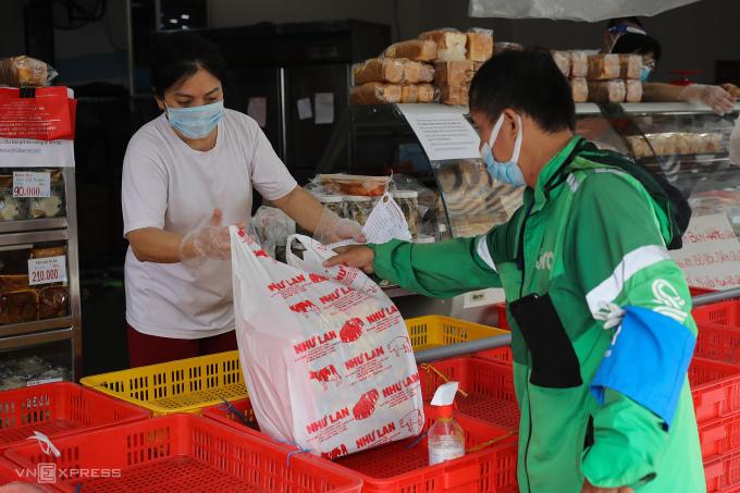 Tài xế giao hàng nhận đơn tại một tiệm bánh ở TP HCM hôm 9/9. Ảnh: Quỳnh Trần