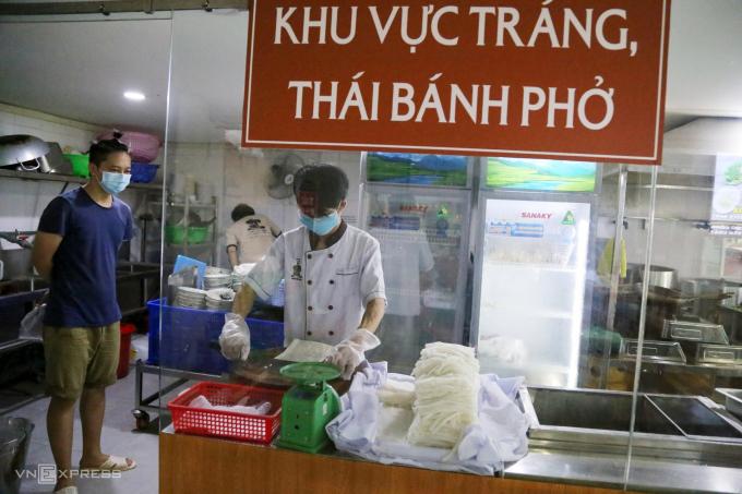 Nhân viên cửa hàng trên đường Bùi Bằng Đoàn, phường Tân Phong, quận 7 cắt bánh phở cho khách hôm 9/9 - ngày đầu hàng quán TP HCM được bán trở lại. Ảnh: Đình Văn
